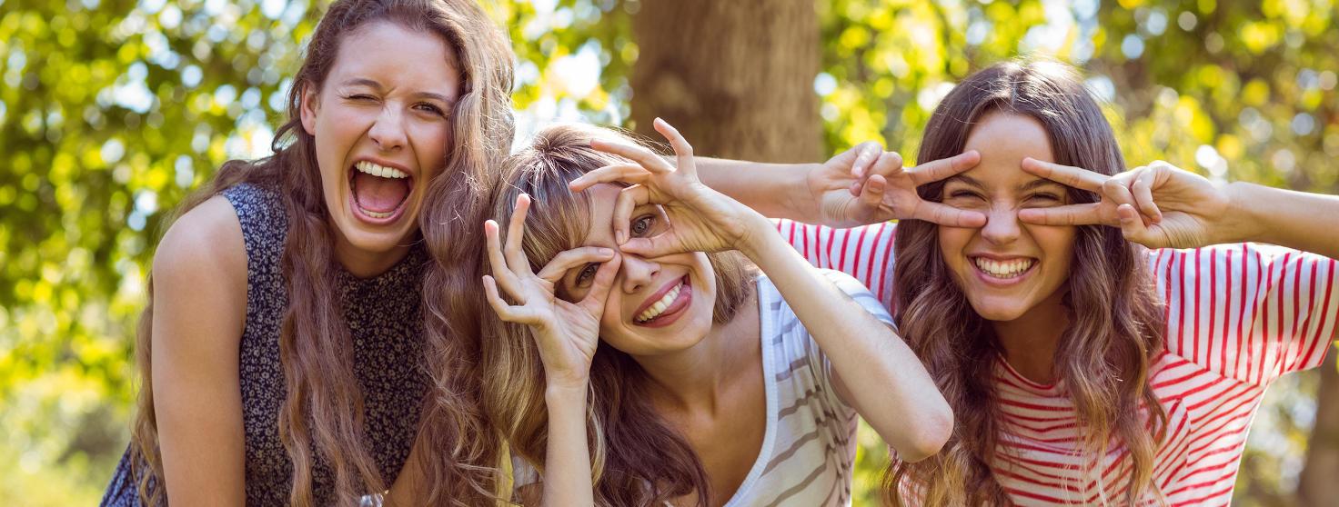 Freundinnen lachen und schneiden herzliche Grimassen während den Vorbereitungen für unser Teambuidling Outdoor Event im Sommer