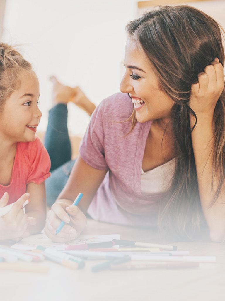 Eine Babysitterin der Babysitterei liegt gemeinsam mit einem jungen Mädchen am Boden während sie mit vielen Buntstiften ein Bild malen und dabei herzlich lachen