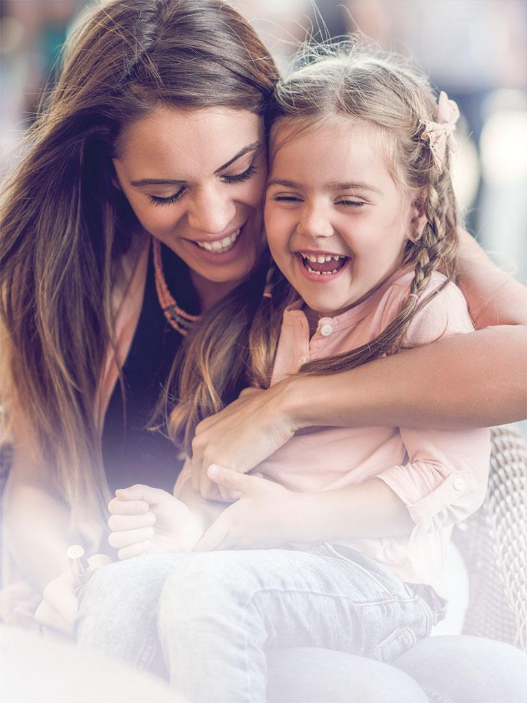 Eine Nanny sitzt lachend mit einem jungen Mädchen auf dem Schoß in einem Café in Graz