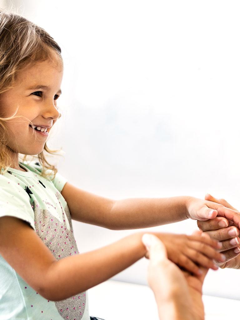 Ein junges Mädchen legt vertrauensvoll die Hände in die ihrer Nanny