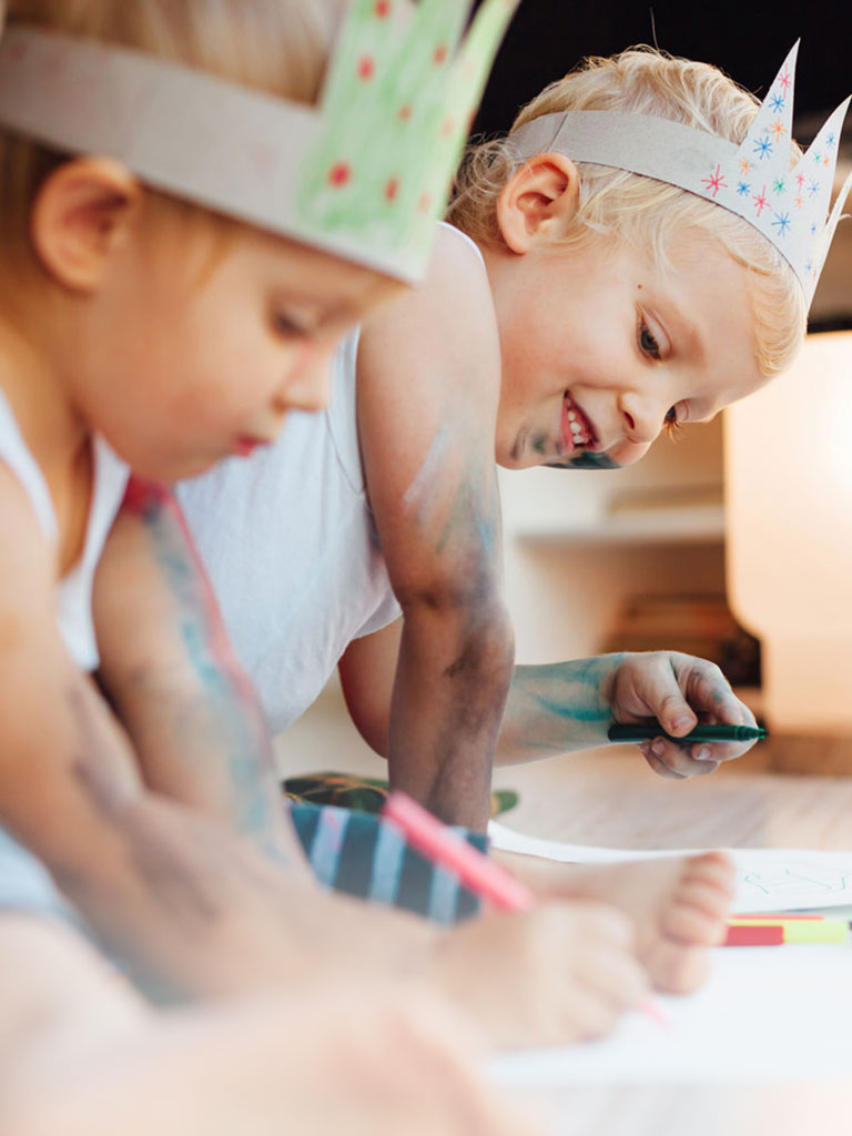 Zwei Kinder sitzen am Boden und malen mit Buntstiften während dem Babysitter Kurs in Salzburg
