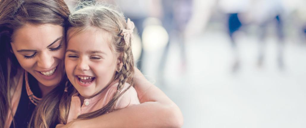 Eine Nanny sitzt lachend mit einem jungen Mädchen auf dem Schoß in einem Café in Salzburg