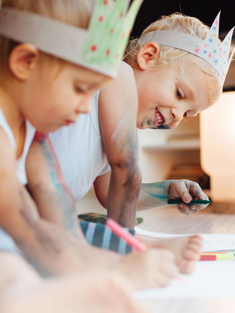 Zwei Kinder sitzen am Boden und malen mit Buntstiften während dem Babysitter Kurs in Wien