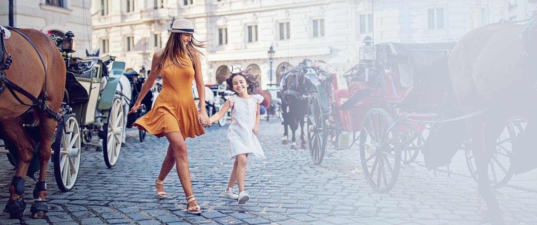 Unsere Hotel Nanny erkundet Hand in Hand mit einem Mädchen die Altstadt Wien und zeigt unserem kleinen Gast auch die Fiaker und Pferde