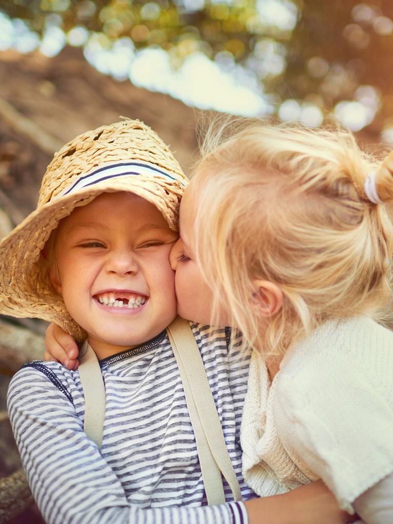 Ein Mädchen gibt einem Jungen ein Küsschen auf die Wange um Danke zu sagen