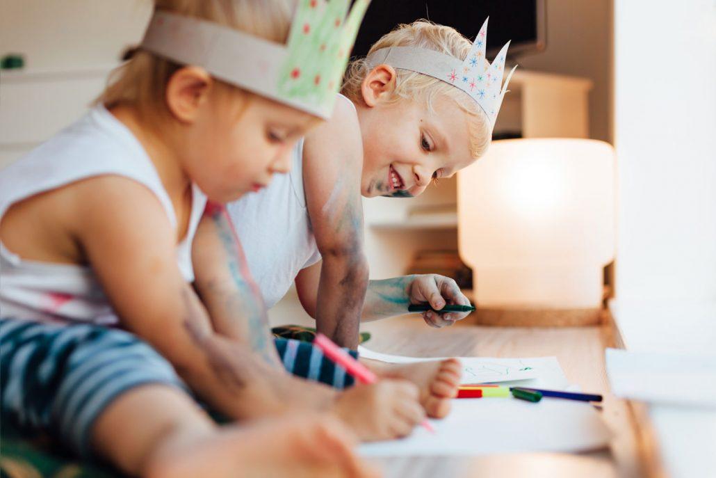 Zwei Kinder sitzen am Boden und malen mit Buntstiften während dem Babysitter Kurs von der Babysitterei Wien