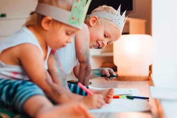 Zwei Kinder sitzen am Boden und malen mit Buntstiften während eines Babysitter Kurses