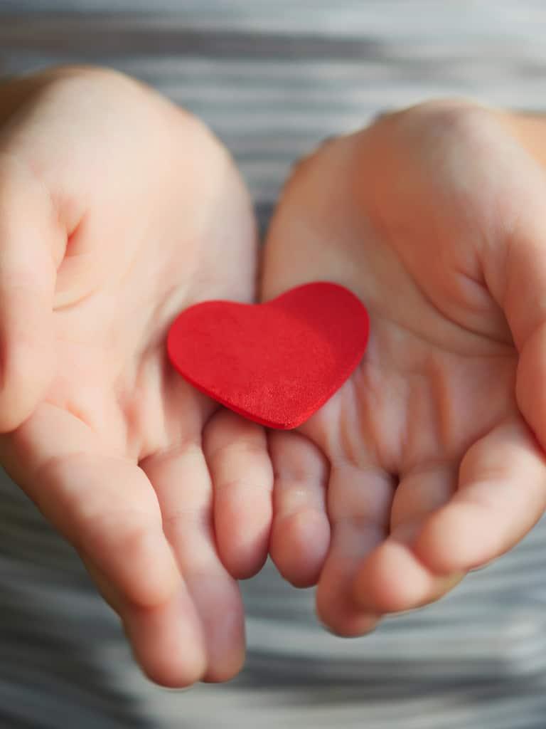 Ein Kind hält behutsam ein rotes Herz aus Filz in den Händen und heisst Sie herzlich willkommen